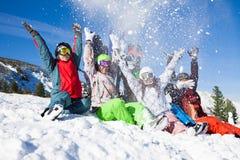 Amis avec des surfs des neiges jetant la neige Photos libres de droits