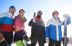 Amis avec des surfs des neiges et des skis Photographie stock