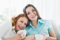 Amis avec des tasses de café appréciant une conversation à la maison Image libre de droits