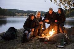 Amis avec des tasses de café se reposant par le feu de camp sur au bord du lac Photographie stock libre de droits