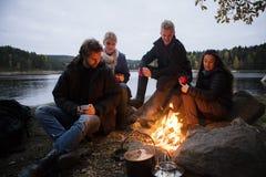 Amis avec des tasses de café se reposant près du feu de camp Image stock