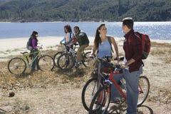 Amis avec des vélos de montagne par le lac Image libre de droits
