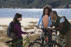 Amis avec des vélos de montagne par le lac Photos stock