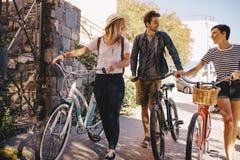 Amis avec des vélos marchant dehors dans la ville Image stock