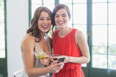 Amis avec des verres de cocktail riant tout en à l'aide du téléphone portable dans le restaurant Image stock