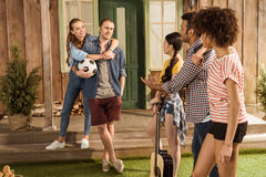 Amis avec du ballon de football et la guitare, parlant et passant le temps ensemble Images libres de droits