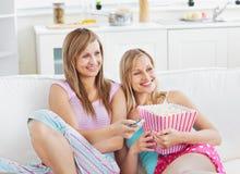 Amis avec du charme regardant la TV manger du maïs éclaté Photographie stock libre de droits