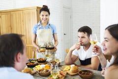 Amis avec du vin blanc grillant au-dessus de la table servie avec la nourriture Images libres de droits