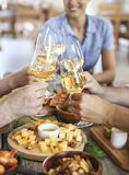 Amis avec du vin blanc grillant au-dessus de la table servie avec la nourriture Image stock