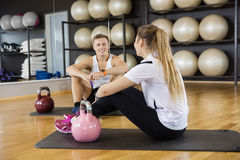 Amis avec Kettlebells sur l'exercice Mat In Gym Photographie stock