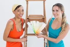 Amis avec l'échelle choisissant la couleur pour peindre une salle Image stock