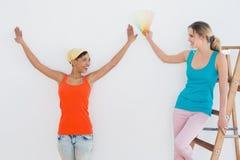Amis avec l'échelle choisissant la couleur pour peindre une salle Photographie stock