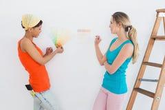 Amis avec l'échelle choisissant la couleur pour peindre une salle Image libre de droits