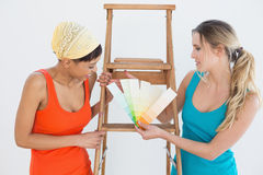 Amis avec l'échelle choisissant la couleur pour peindre une salle Photos stock