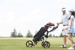 Amis avec l'équipement parlant tout en marchant au terrain de golf contre le ciel clair Images stock