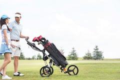 Amis avec l'équipement parlant tout en marchant au terrain de golf contre le ciel clair Image stock