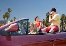 Amis avec l'appareil-photo conduisant dans la voiture convertible Photo stock