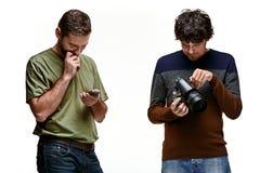 Amis avec l'appareil-photo et le téléphone sur le blanc Image libre de droits