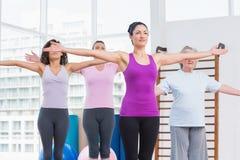 Amis avec l'exercice tendu par bras dans le gymnase Images libres de droits