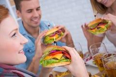 Amis avec l'hamburger à disposition Images stock