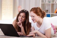 Amis avec l'ordinateur dans le lit Photo stock