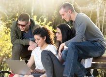 Amis avec l'ordinateur portable sur le banc Photos stock