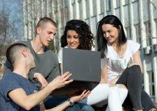 Amis avec l'ordinateur portable sur le banc Image libre de droits