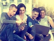 Amis avec l'ordinateur portable sur le banc Images libres de droits