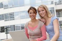 Amis avec l'ordinateur portatif devant la construction Photographie stock libre de droits