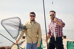 Amis avec la canne à pêche, les poissons et l'attirail sur le pilier images stock