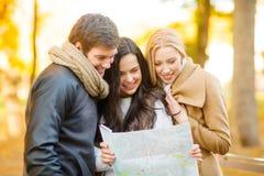 Amis avec la carte de touristes en parc d'automne Photo libre de droits