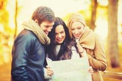 Amis avec la carte de touristes en parc d'automne Photographie stock libre de droits