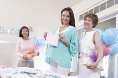 Amis avec la femme enceinte tenant le cadeau de fête de naissance Image libre de droits
