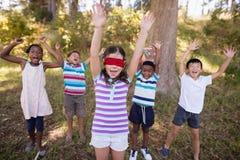 Amis avec la fille bandée les yeux encourageant dans la forêt Photos libres de droits