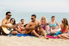 Amis avec la guitare à la plage Images libres de droits