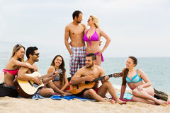Amis avec la guitare à la plage Image libre de droits