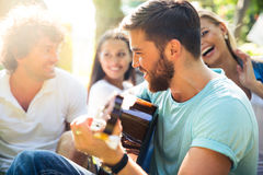 Amis avec la guitare ayant l'amusement extérieur Photo stock