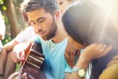 Amis avec la guitare ayant l'amusement extérieur Photos stock