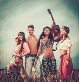 Amis avec la guitare dans un domaine de blé Photographie stock libre de droits