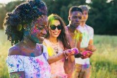 Amis avec la peinture colorée sur l'habillement et corps au festival de holi Photos stock