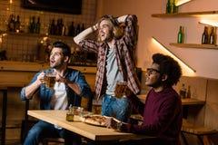 Amis avec la pizza et la bière dans la barre Image stock