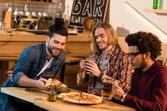 Amis avec la pizza et la bière dans la barre Images stock
