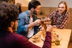 Amis avec la pizza et la bière dans la barre Photos libres de droits