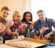 Amis avec la pizza et les bouteilles de la boisson Photos libres de droits