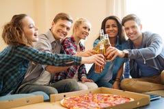 Amis avec la pizza et les bouteilles de la boisson Photographie stock libre de droits
