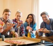 Amis avec la pizza et les bouteilles de la boisson Images libres de droits