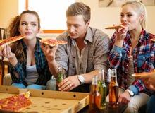 Amis avec la pizza et les bouteilles de la boisson Photographie stock