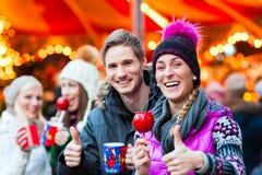 Amis avec la pomme de sucrerie et le lait de poule sur le marché de Noël Photographie stock libre de droits