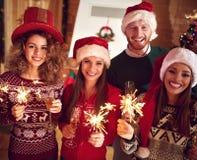 Amis avec le champagne et les étincelles pendant la nouvelle année Photo stock