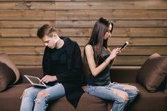Amis avec le comprimé et le téléphone à la maison Images libres de droits